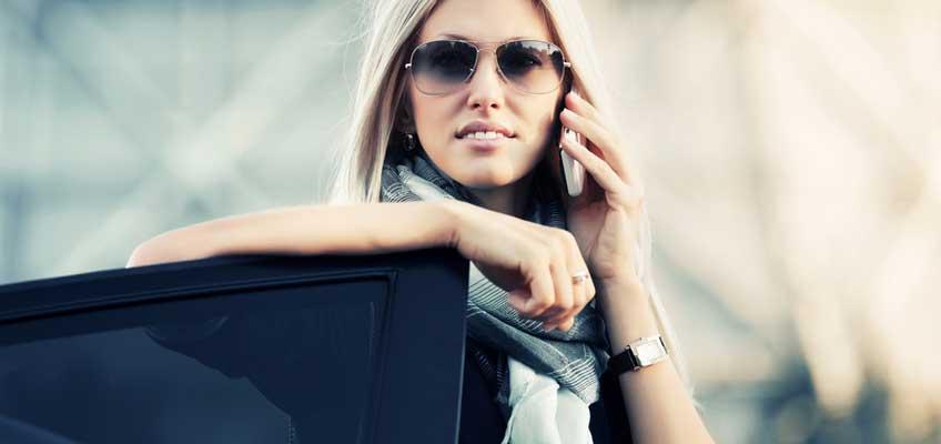 Kvinna lutar sig mot bildörr och pratar i telefon
