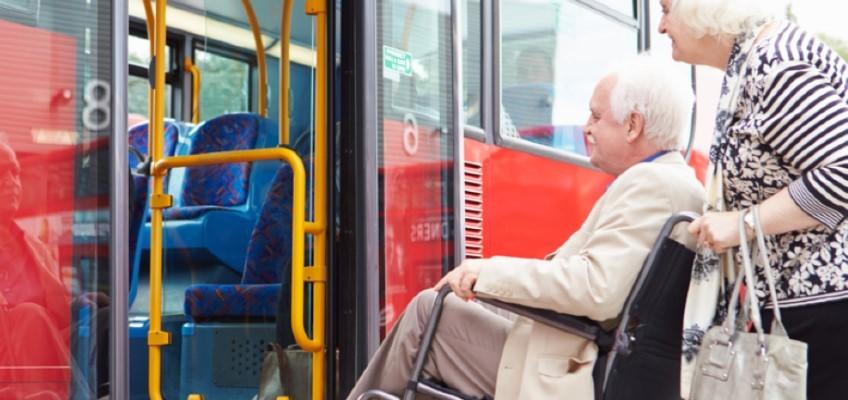 Man i rullstol och kvinna på väg in i färdtjänstbil
