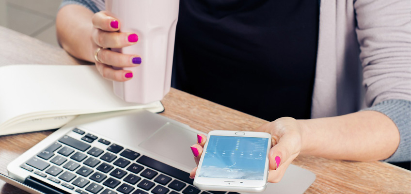 Kvinna vid dator och telefon i handen