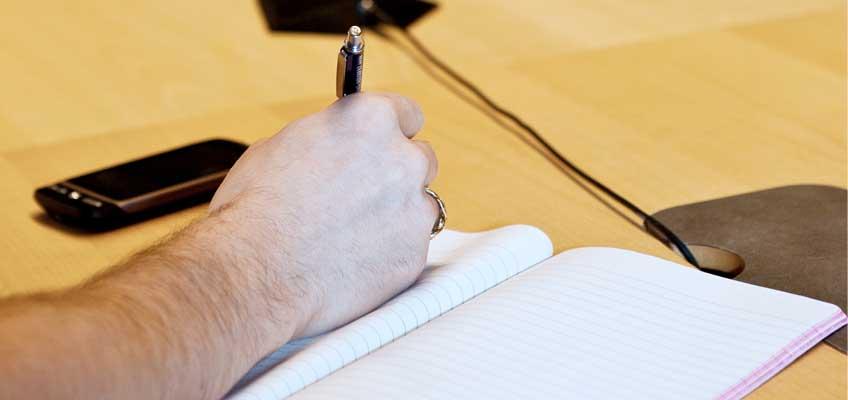 En hand gör anteckningar