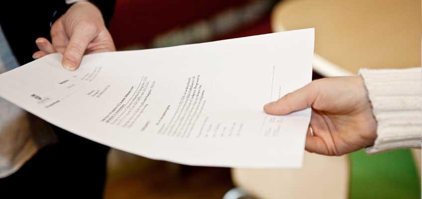 Två händer håller i ett dokument