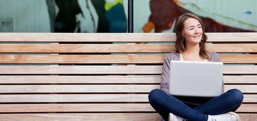 Flicka på bänk med dator i knät