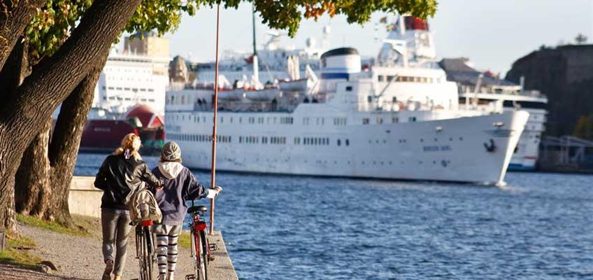 Personer leder cyklar vid en kanal med skepp i