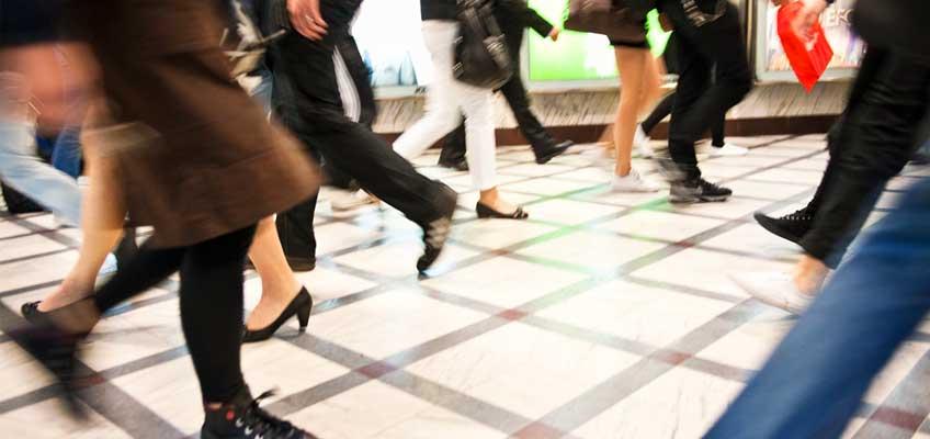 Flera par fötter som går på golv