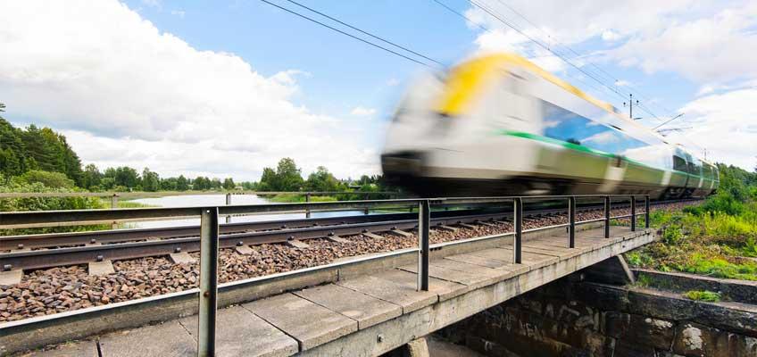 Tåg på bro i sommarlandskap
