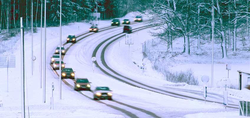Väg med bilar i snötäckt landskap
